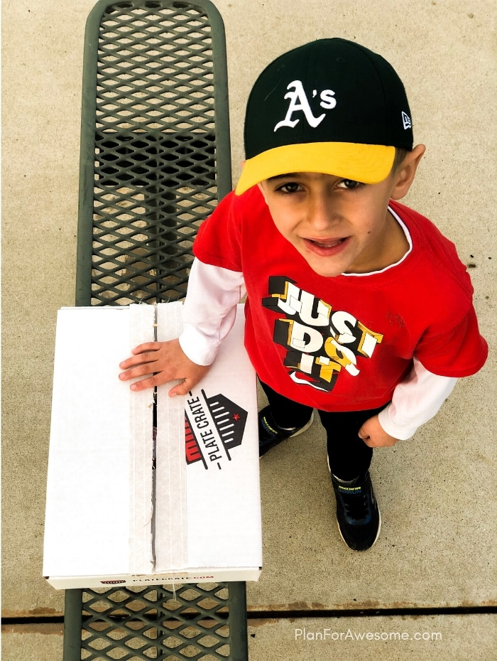 Happy little boy with his baseball subscription box!  The BEST GIFT EVER for Baseball Lovers (plus a $20 off coupon) - seriously the coolest and the easiest gift idea for baseball lovers and players!  A surprise box full of baseball gear, apparel, training aids, accessories, and snacks - what's not to love?!  #baseballgiftideas #baseballmom